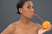 Woman drinking from an orange