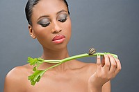 Woman looking at a snail on a stick of celery