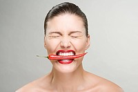 Woman with a red chili pepper in her mouth