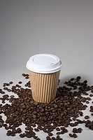 A paper cup on coffee beans