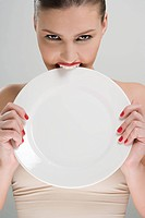 Woman biting a plate