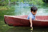 Guatemala, Rio Dulce, young boy in canoe