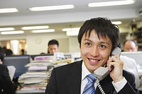 Businessman Smiling While Talking On Telephone In Office