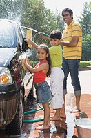 Man and his children washing a car, New Delhi, India