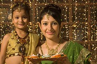 Woman with her daughter holding a traditional Diwali thali