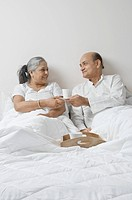 Couple drinking coffee on the bed