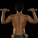 Rear view of a man exercising with dumbbells