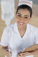 Female nurse adjusting a saline drip, Gurgaon, Haryana, India