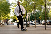 African businessman riding children's push scooter