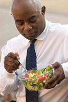 African businessman eating salad