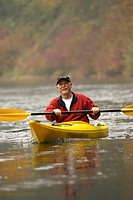 Man rowing kayak in river in autumn