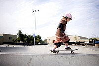 Girl skating on skateboard in skate park