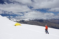 Hiker walking toward tent in snowy mountains (thumbnail)
