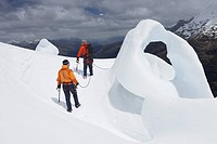 Two hikers going past ice formation in mountains back view
