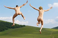 Young naked couple running and jumping in mountain field back view