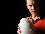 Rugby player holding ball close_up portrait