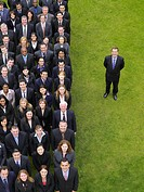 Business man standing next to large group of business people in formation elevated view portrait (thumbnail)