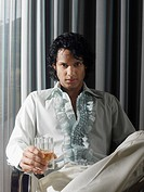 Man sitting with alcoholic drink in front of curtains (thumbnail)
