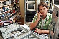 Man using phone surrounded by computer equipment