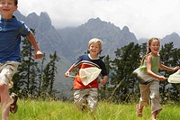 Three children 7_9 running through field with butterfly nets