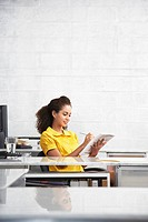 Young woman sitting at desk in office writing in notepad