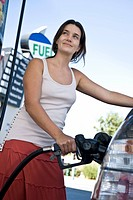 Smiling woman refueling car at natural gas station