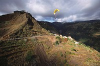 Paraglider over mountains, South coast near Calheta, Madeira, Portugal