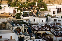 View over town in the evening, people sitting on terraces of restaurants, Lindos, Rhodes, Greece
