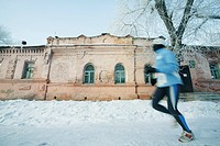 Runner running over snow covered street, Omsk, Siberia, Russia