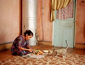 Woman cutting vegetables in front of curious cat, Uzbekistan