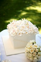 Square wedding cake with a mass of roses