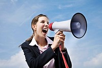 portrait of young businesswoman shouting through megaphone