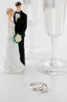 Wedding rings by bride and groom cake toppers and wineglasses