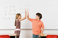 Students high_fiving after completing math at whiteboard