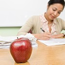 Teacher grading papers with apple in foreground