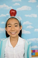 Girl in classroom balancing apple on her head