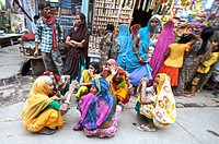 India, Vrindavan, a group of married women kneeling in the street