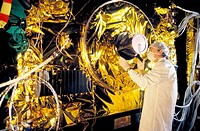 Satellite construction. Mylar insulation being added to a satellite during its construction. This material, also known as polyethylene terphthalate Bo...