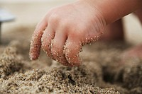 Child's Hand Digging in Sand