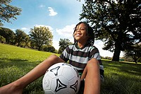 Low angle view of boy sitting with soccer ball between his legs, Zoolake Park, Johannesburg, Gauteng, South Africa