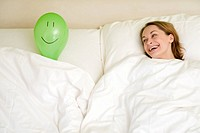 young woman with balloon face in bed