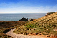 Walkers on the coastal footpath above Durdle Door on Dorset's Jurassic Coast near Lulworth Cove