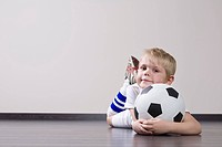 Boy lying on floor and holding soccer ball portrait