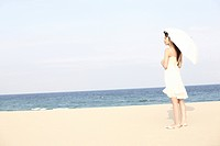 Japanese woman put up an sunshade on the beach