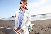 Office lady operating a PC on a beach