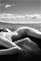 Close up of nude Caucasian mid adult woman draped over rock with at coast in background