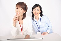 Business lady and the fellow worker who sit down before a laptop computer