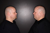 Caucasian bald mid adult identical twin men standing face to face staring