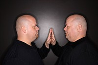Bald mid adult identical twin men standing face to face with hands touching.