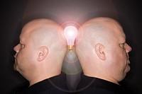 Caucasian mid adult identical twin men standing back to back and balancing a lightbulb between them